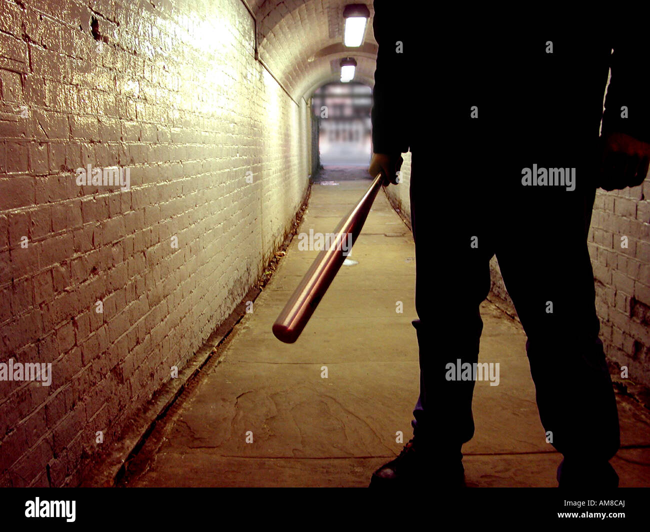 Unidentified thug with a baseball bat in a tunnel - Stock Image
