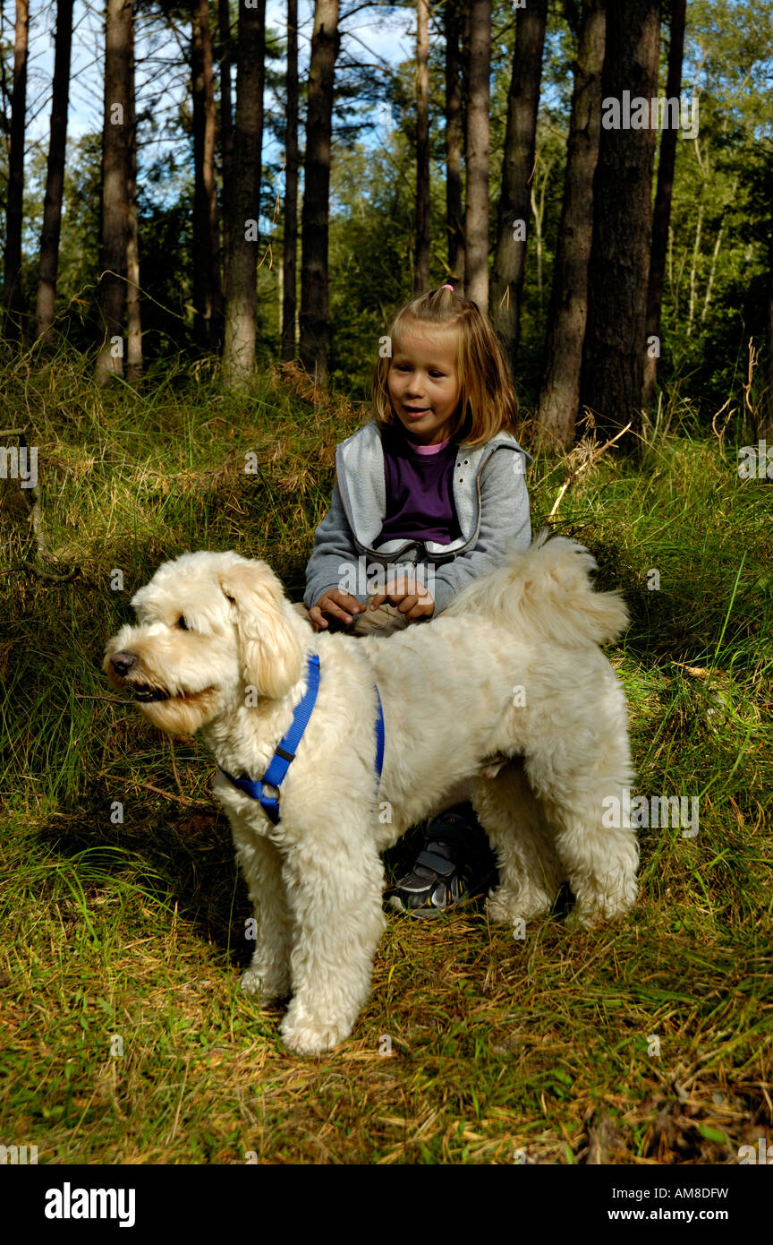 Young girl taking a rest with pet dog in a forest. - Stock Image