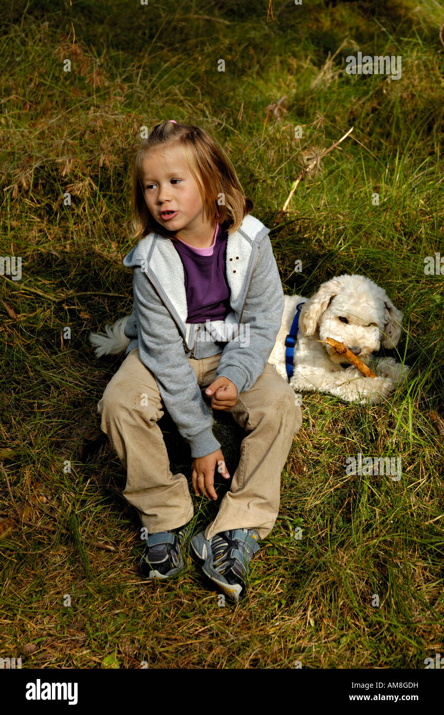 Young girl with pet dog outdoors. - Stock Image