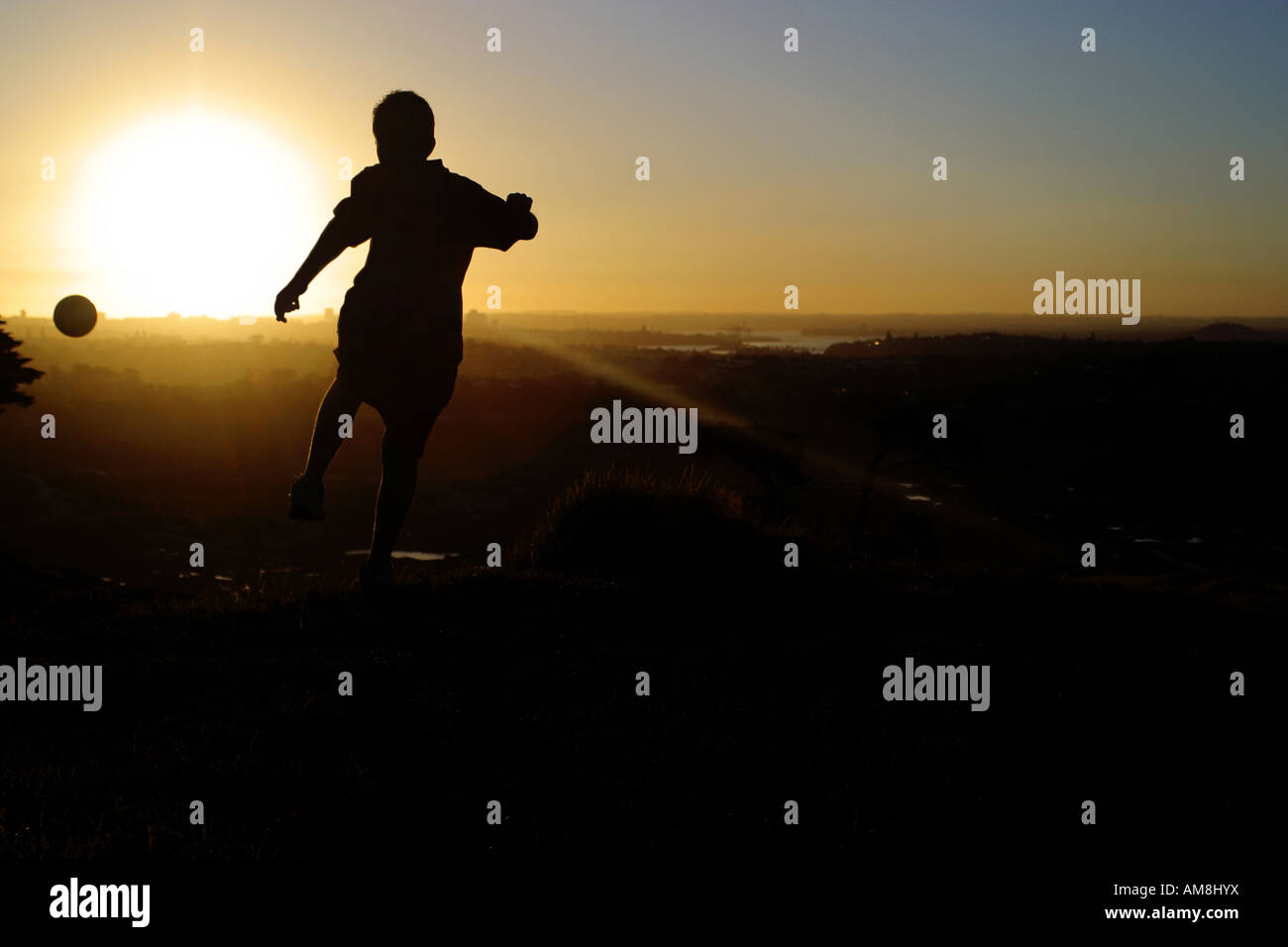 young man kicking a football into the sunset - Stock Image