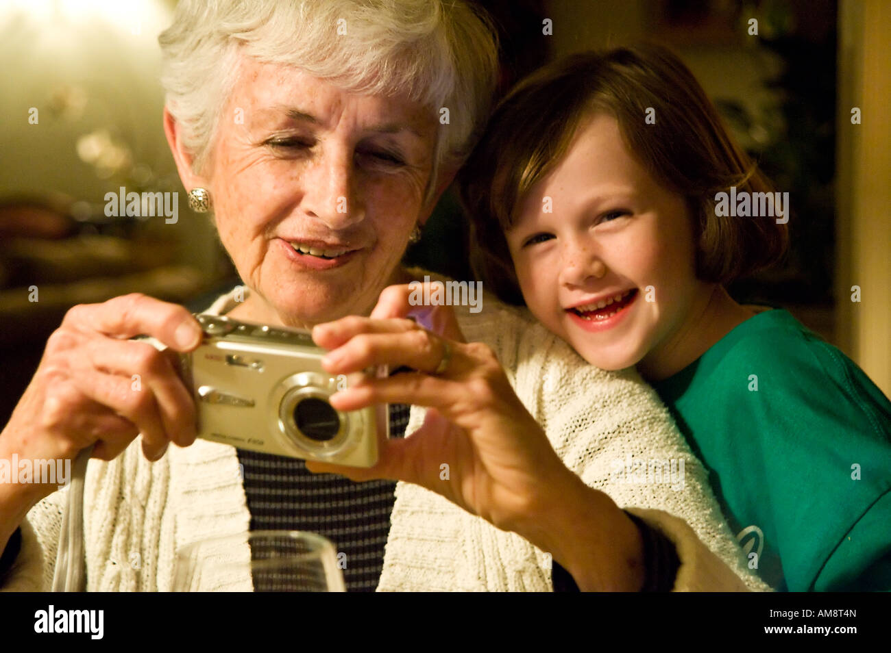 Grandmother and granddaughter enjoy a digital point and shoot camera - Stock Image
