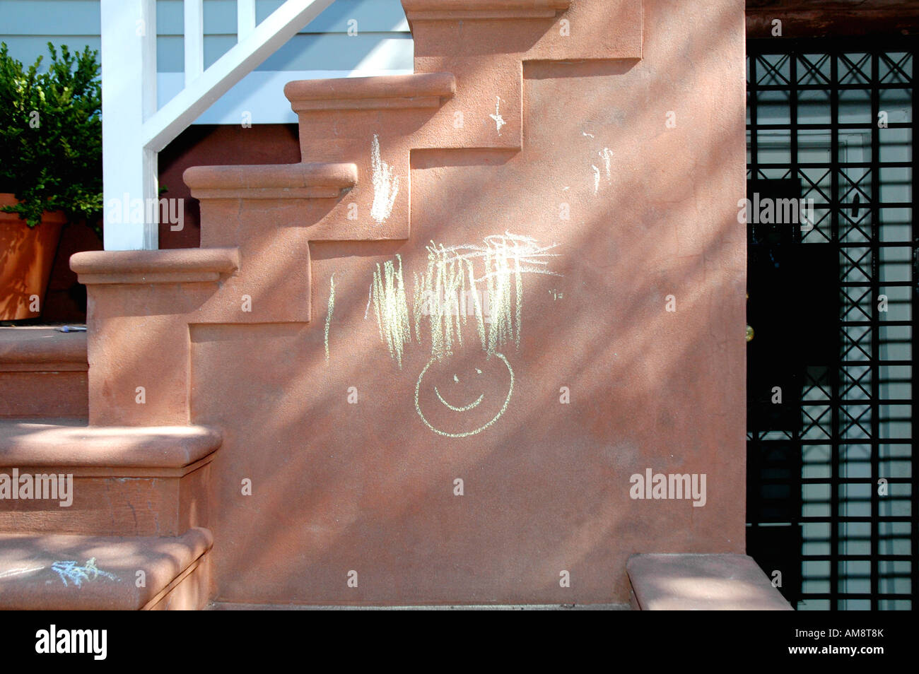 young childs chalk drawing of a smiley face on residential cement stairway - Stock Image