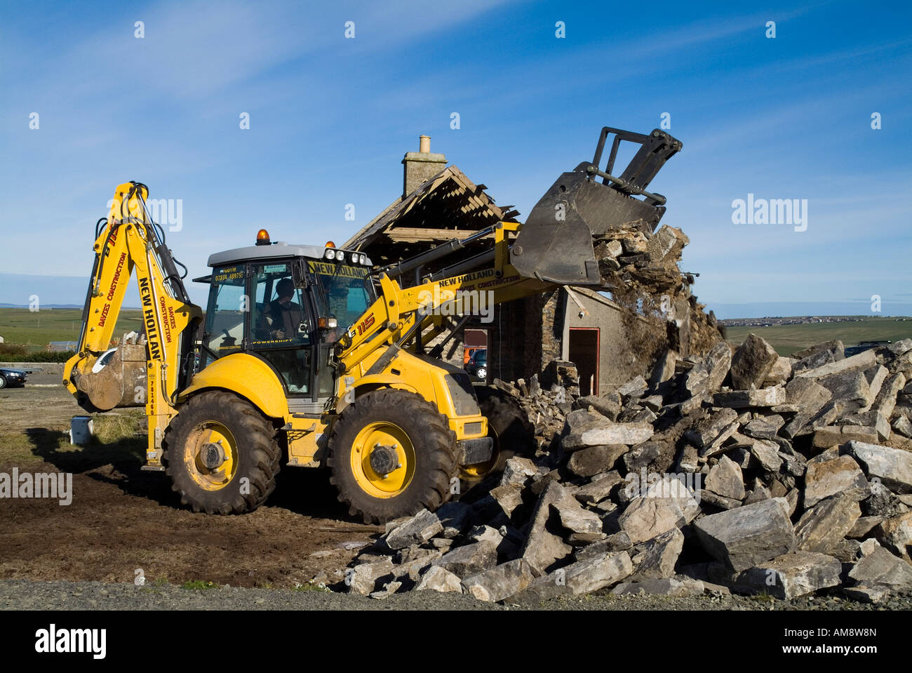 dh Demolition Digger tractor CONSTRUCTION UK Old building action clear debris demolished demolishing houses - Stock Image
