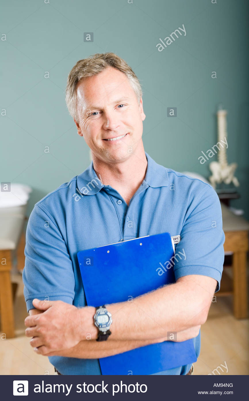 Male physical therapist holding chart - Stock Image