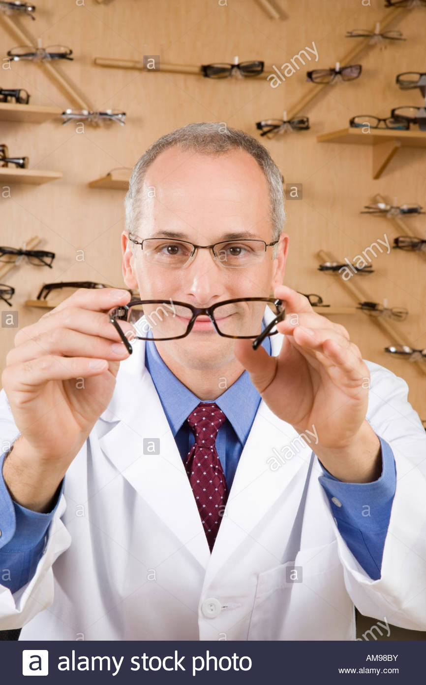 Male optician holding eye glasses - Stock Image