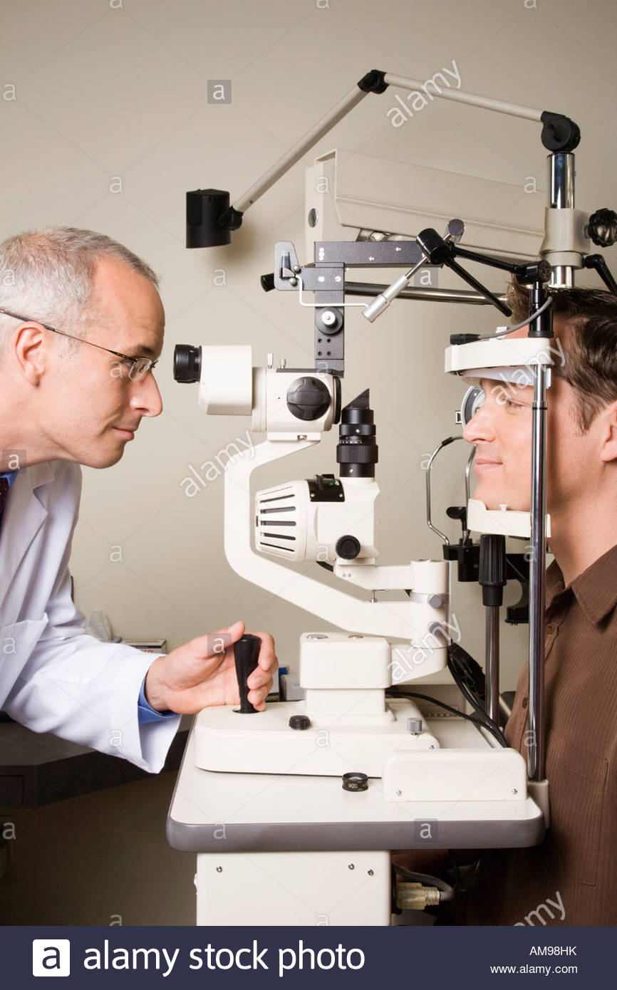 Male ophthalmologist examining man - Stock Image