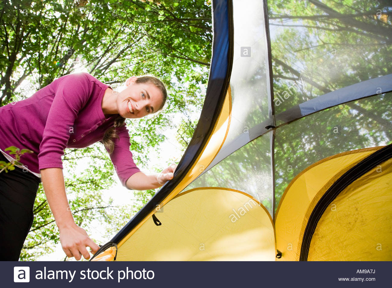 Woman zipping up tent - Stock Image