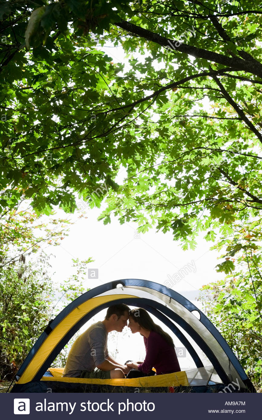 Couple sitting in tent - Stock Image