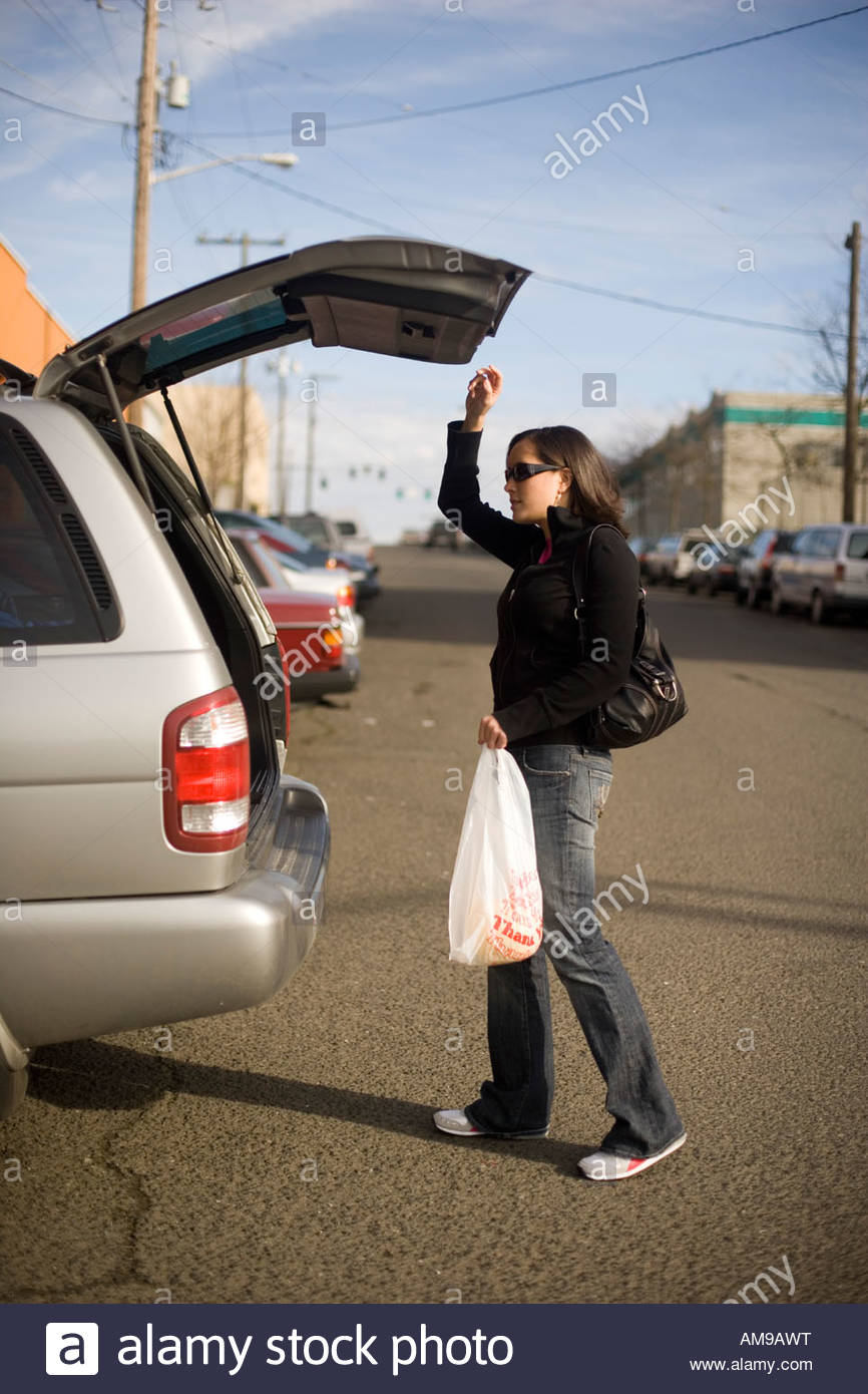 Woman opening trunk of car Stock Photo