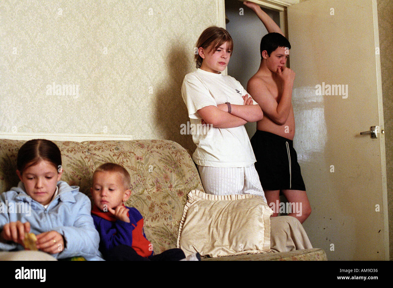 Four siblings of large family hanging around at home - Stock Image