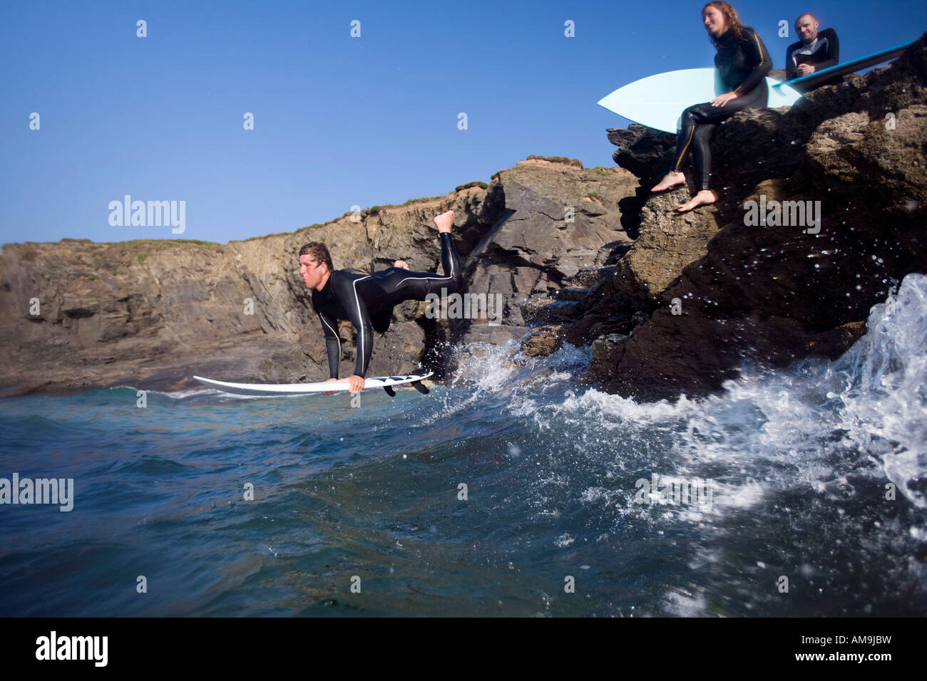 Man jumping into water on surfboard with two people sitting on large rocks smiling. - Stock Image