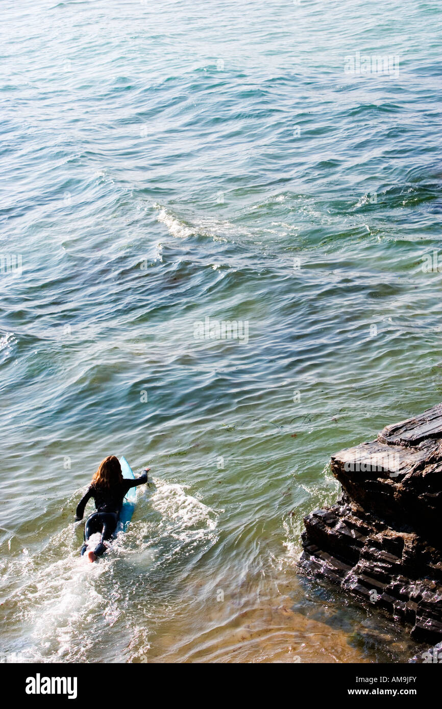 Woman lying on surfboard in the water. - Stock Image