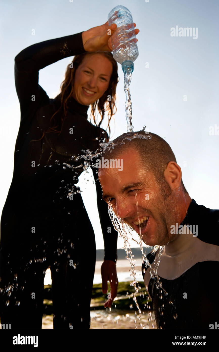 Woman pouring water over laughing man's head. - Stock Image