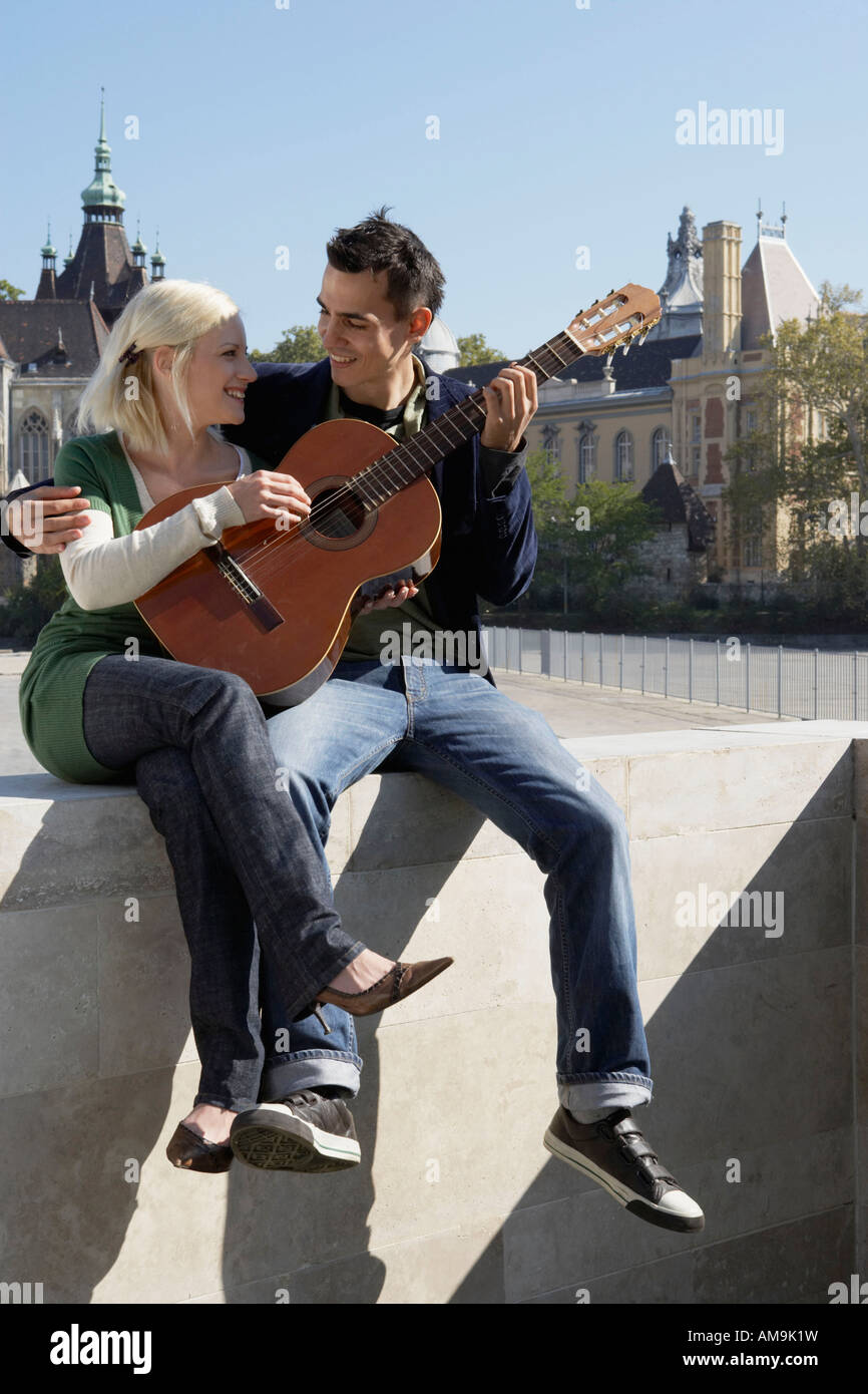 Couple playing guitar outdoors smiling. - Stock Image