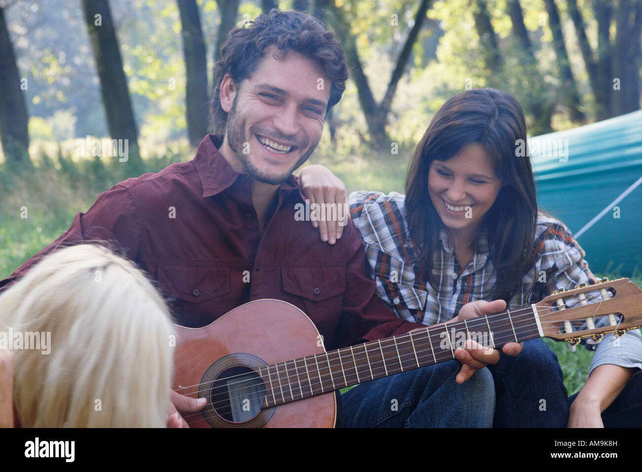 Man at campsite playing guitar with two woman listening and smiling. - Stock Image