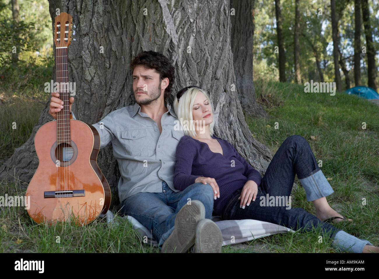 Man holding a guitar with sleeping woman leaning on him. - Stock Image