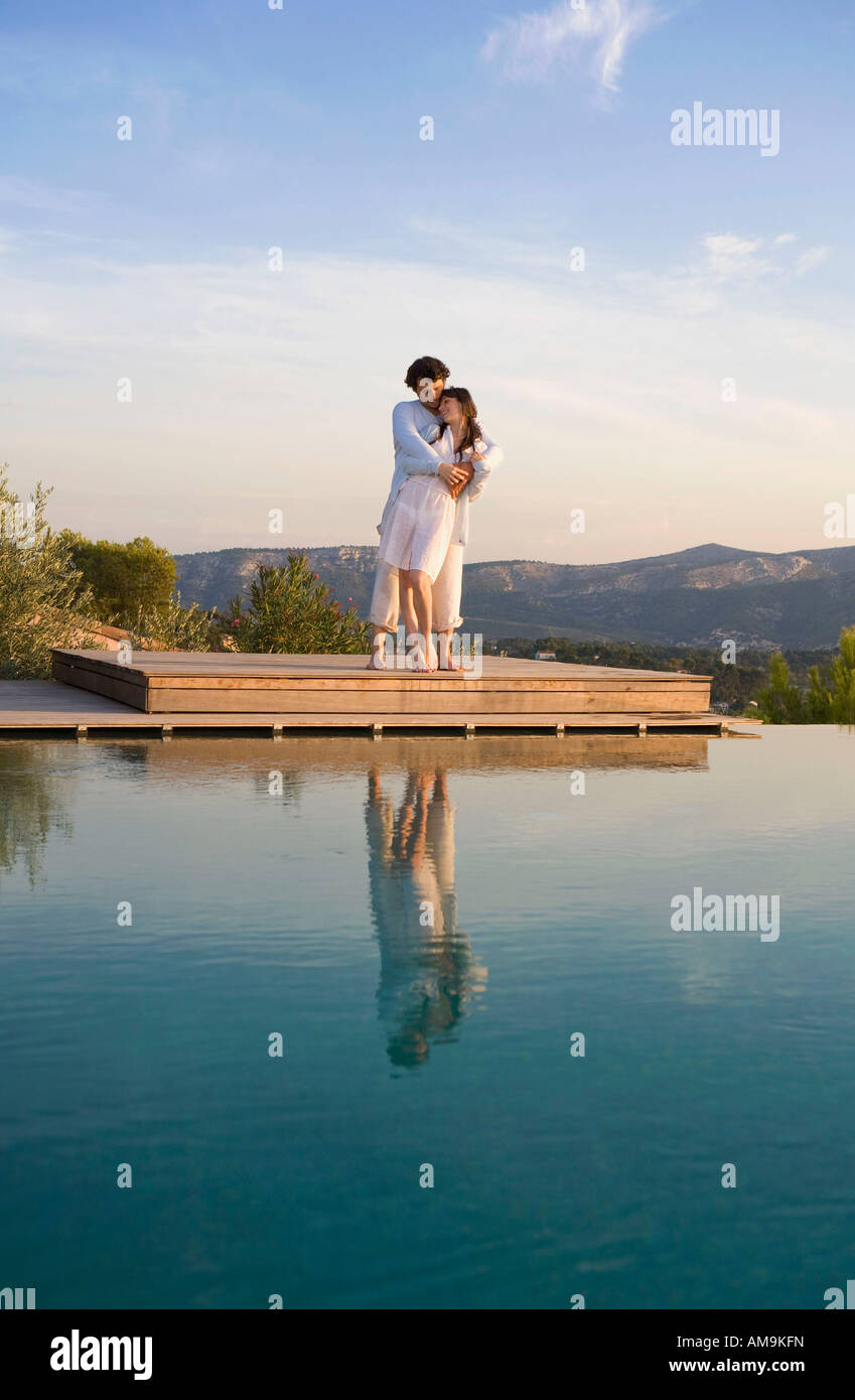 Loving couple embracing on wood dock in nature . - Stock Image