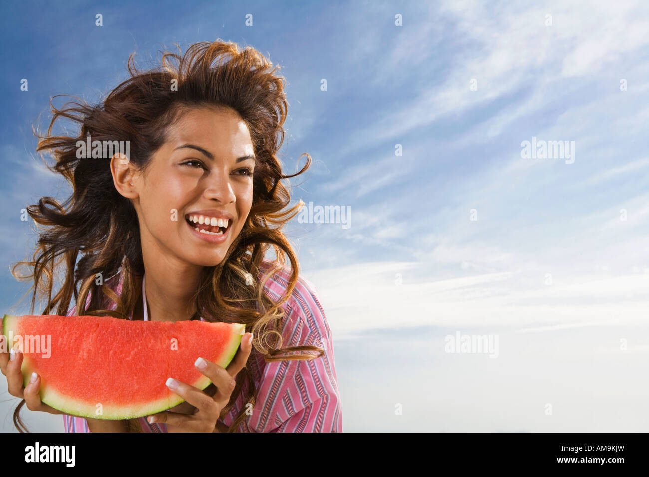 Woman laughing and eating watermelon outdoors. - Stock Image