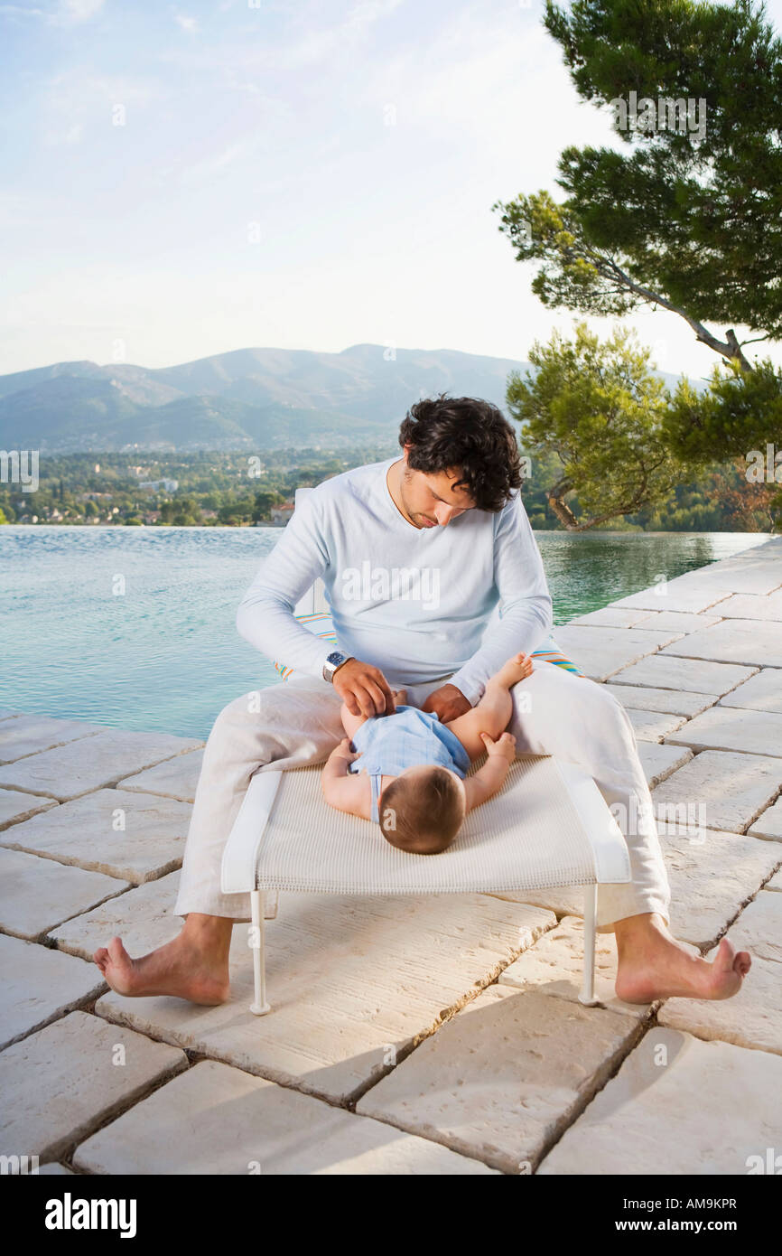 Man changing a baby's diaper by an infinity pool. - Stock Image
