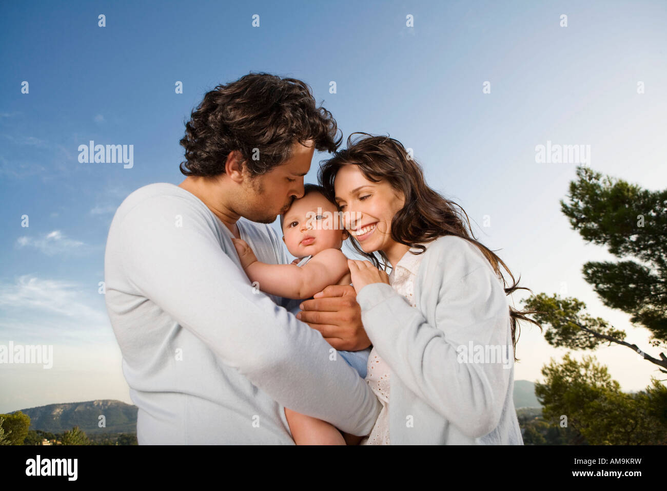 Couple holding a baby outdoors with the man kissing him. - Stock Image