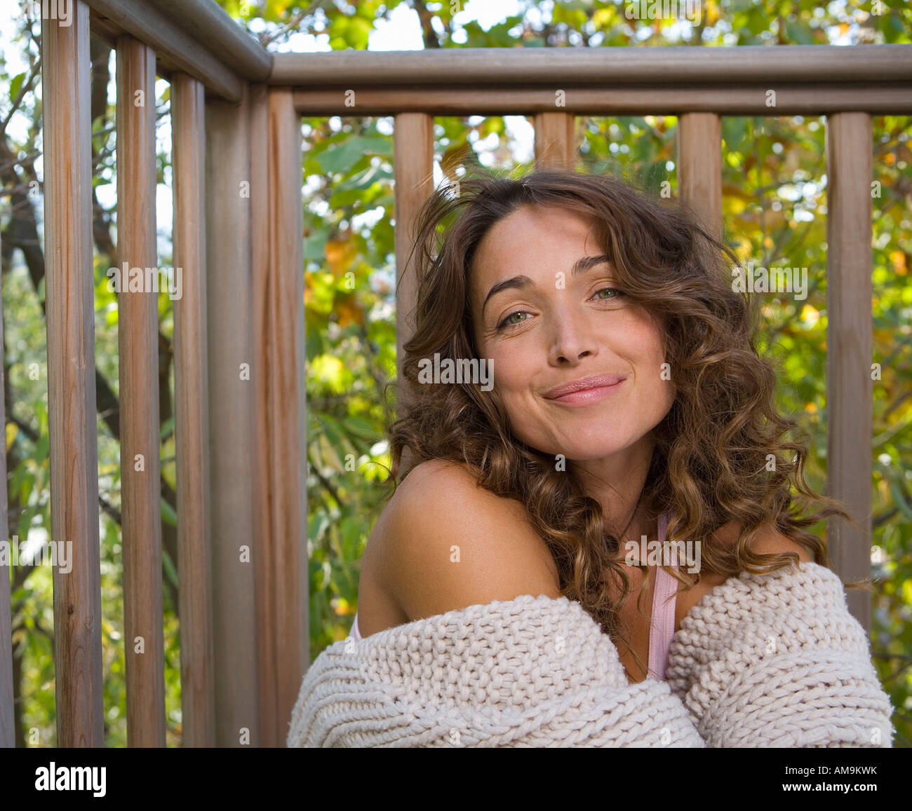 Woman sitting on balcony smiling. Stock Photo