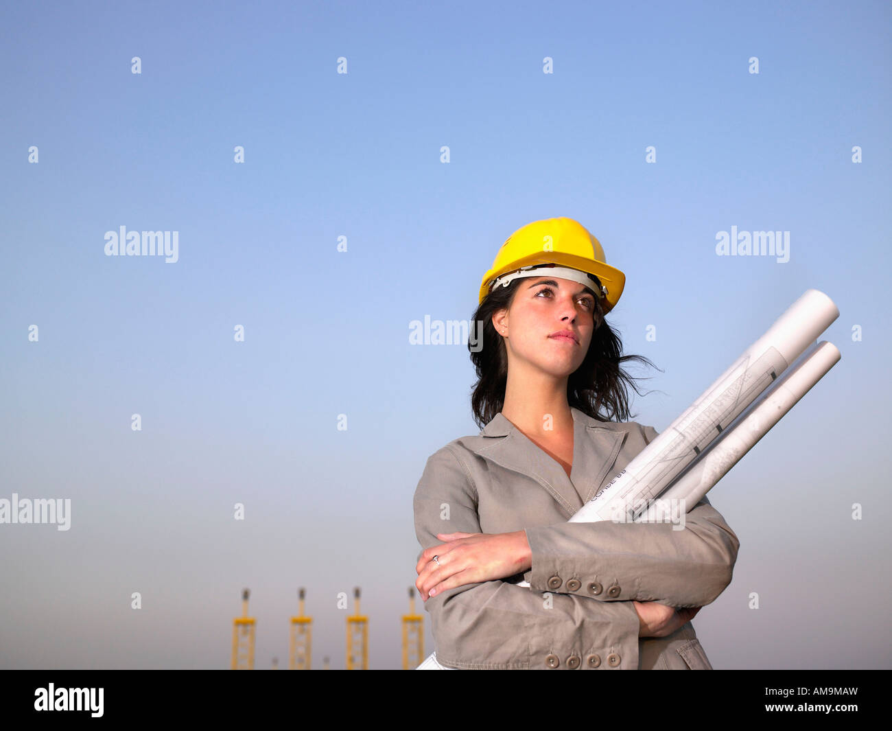 Woman in hard hat holding drafts with towers in background. Stock Photo
