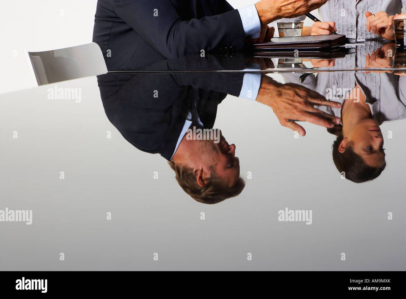Two business people's reflection in a table. - Stock Image
