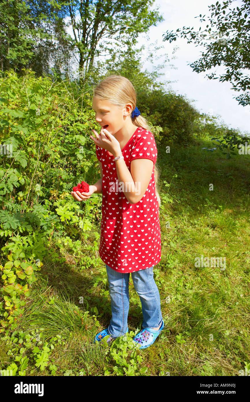 Young girl eating fresh raspberries smiling. - Stock Image