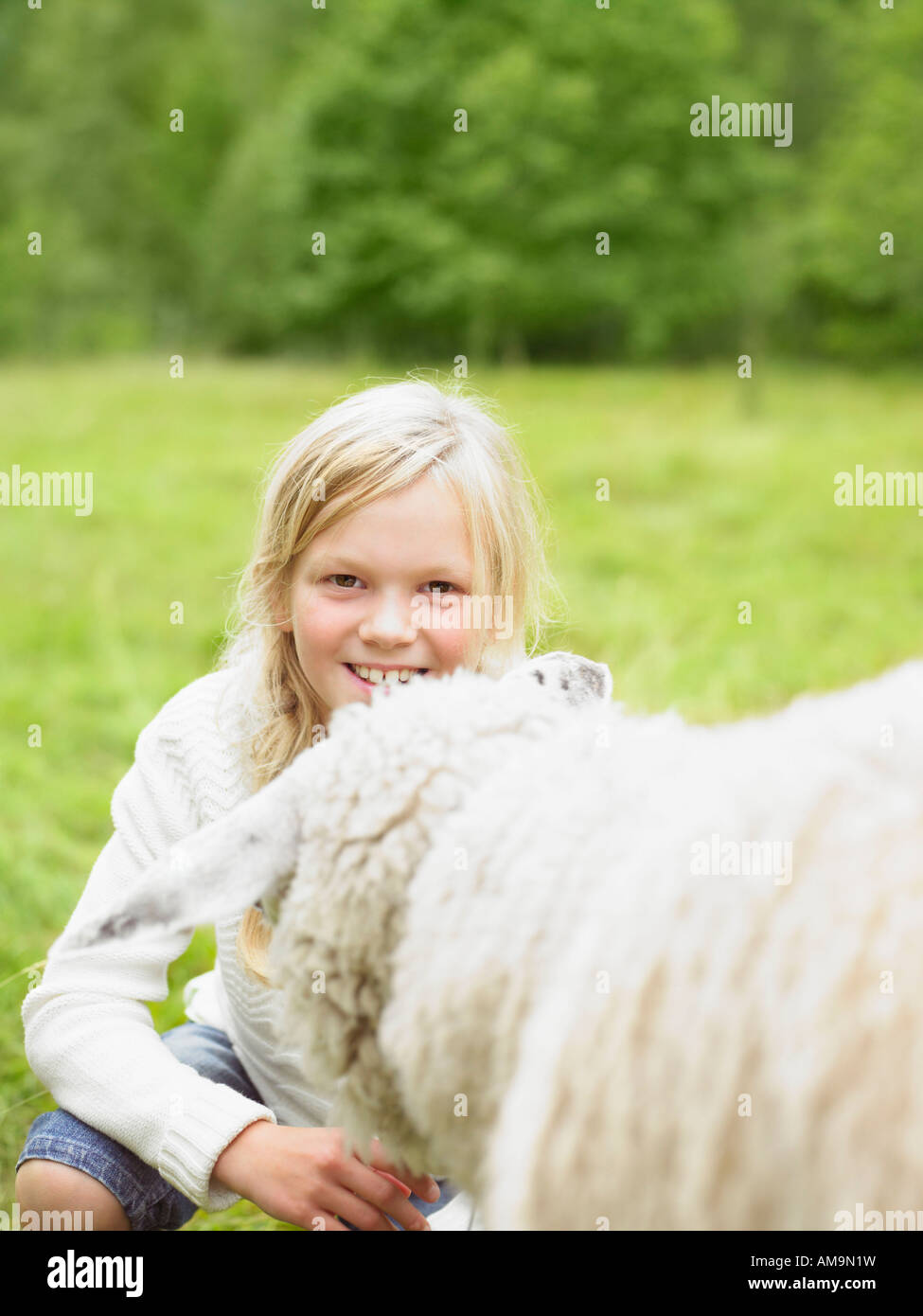 Young girl smiling and crouching by a sheep in a field. - Stock Image
