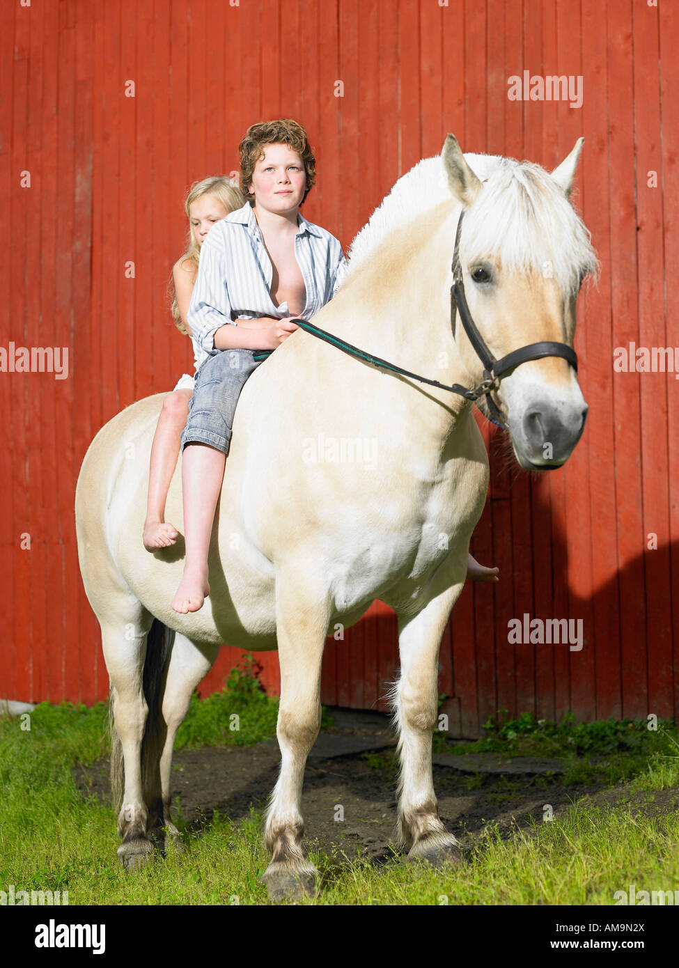 Young boy and young girl on a horse in front of a red wall. Stock Photo