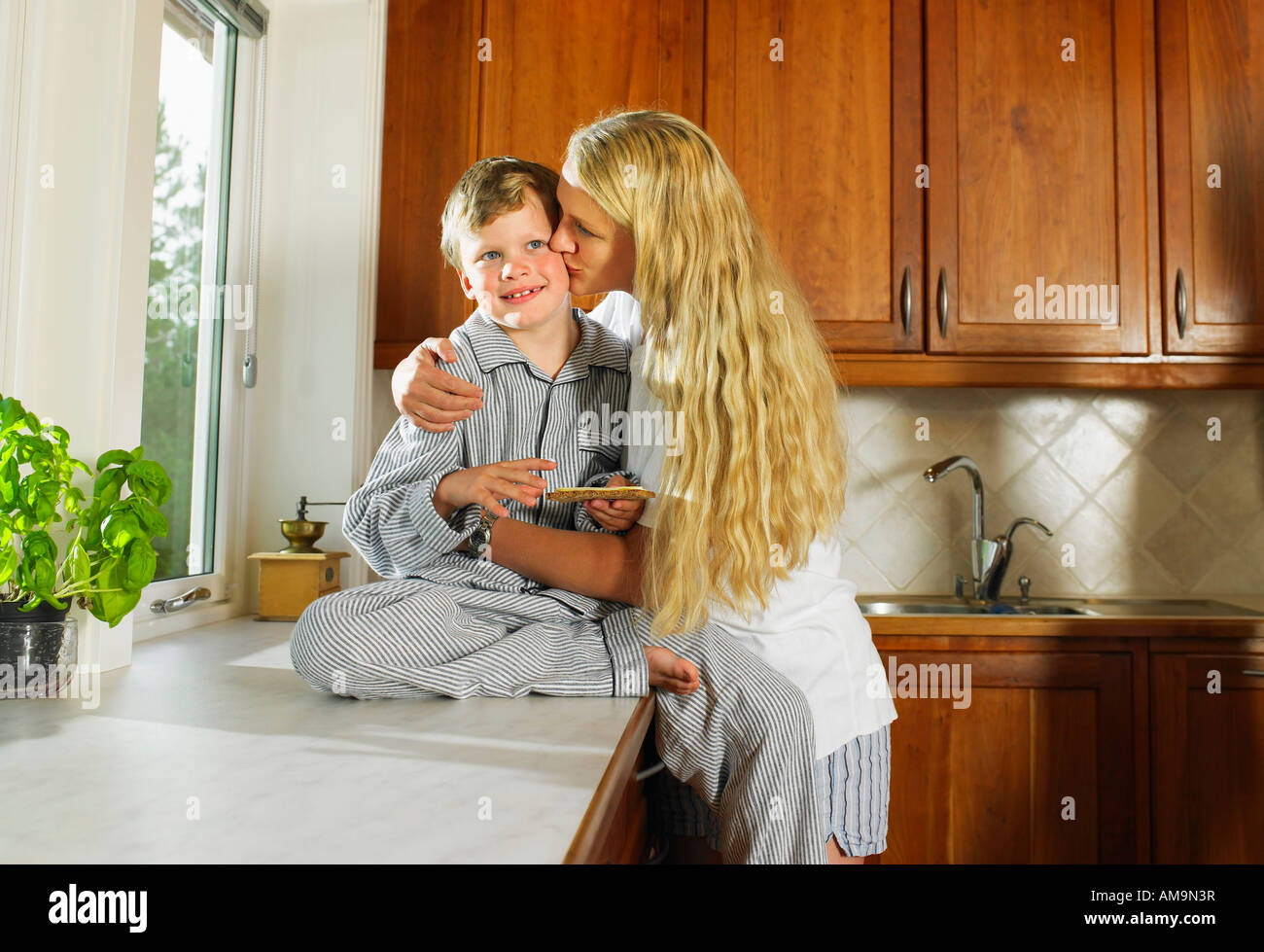 Woman kissing young boy holding sandwich in kitchen. - Stock Image