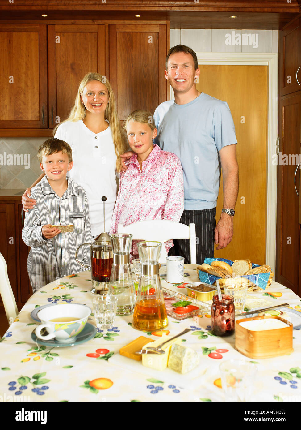 Family standing in kitchen smiling with breakfast on table. - Stock Image