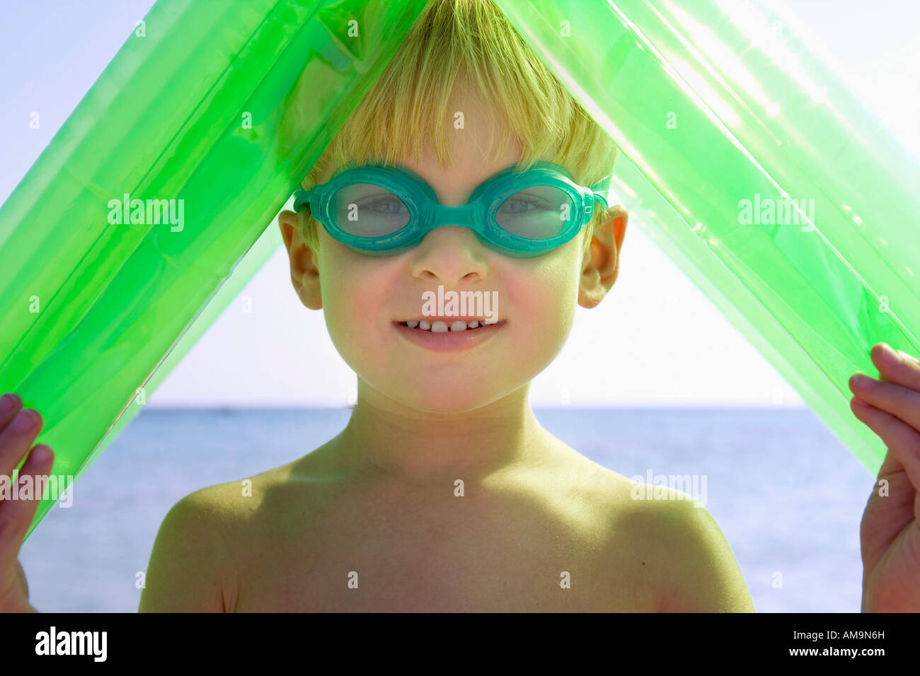 Young boy wearing swim goggles and holding an inflatable raft over his head. Stock Photo