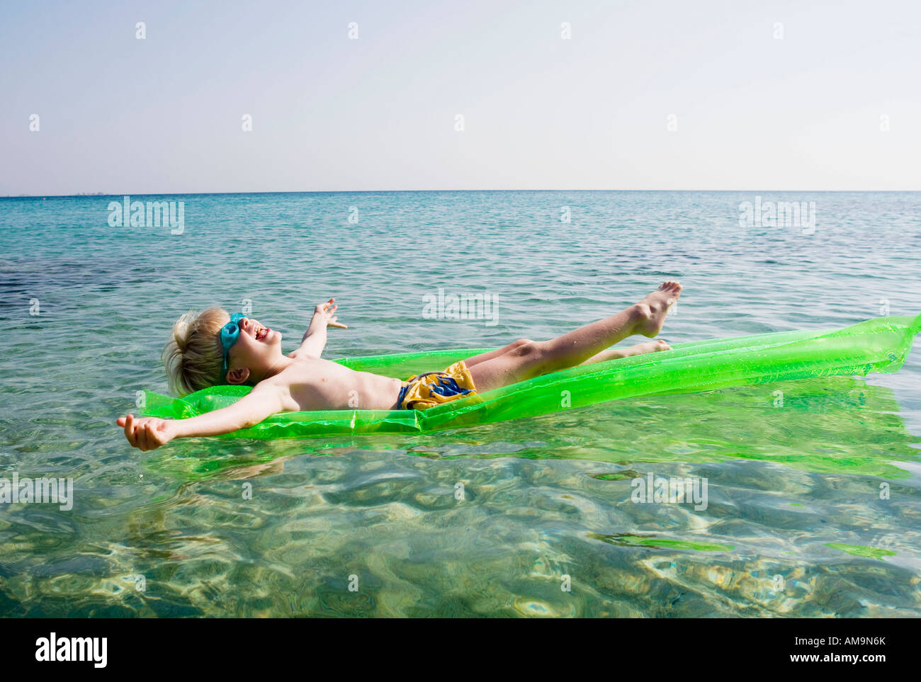 Young boy on an inflatable raft in the water smiling. Stock Photo