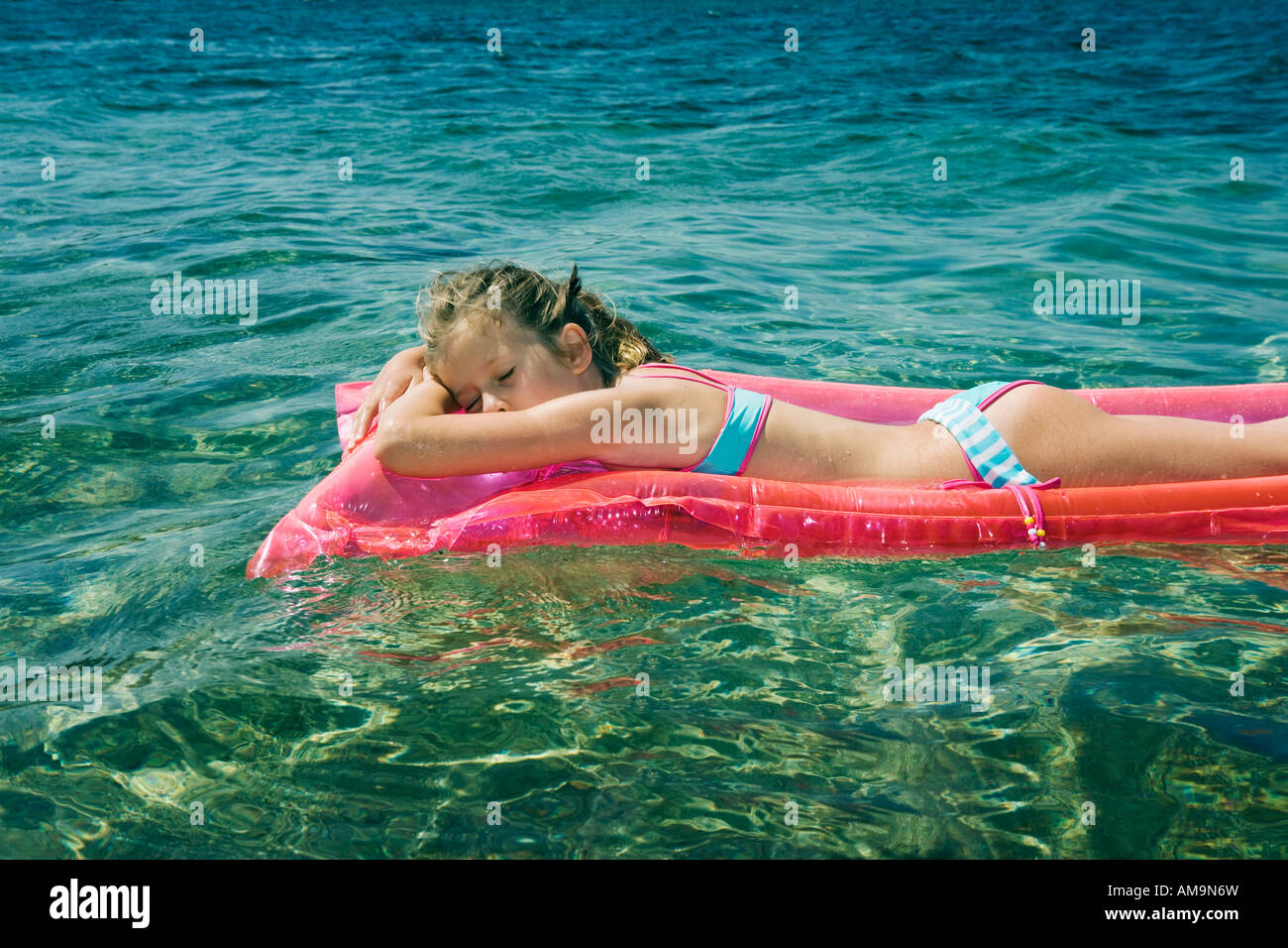Young girl sleeping floating on an inflatable raft. Stock Photo