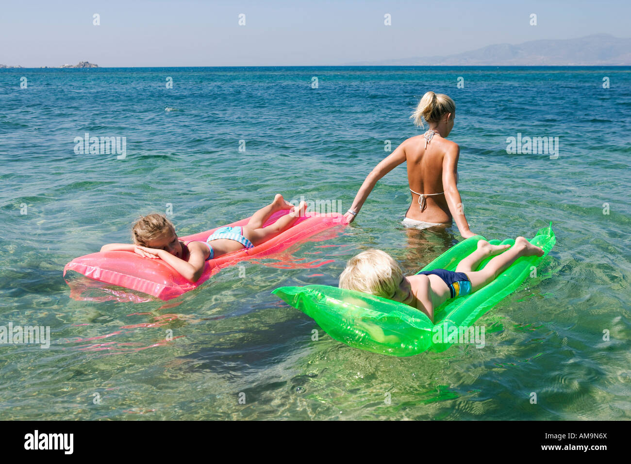 Woman pulling young boy and young girl on inflatable rafts. Stock Photo
