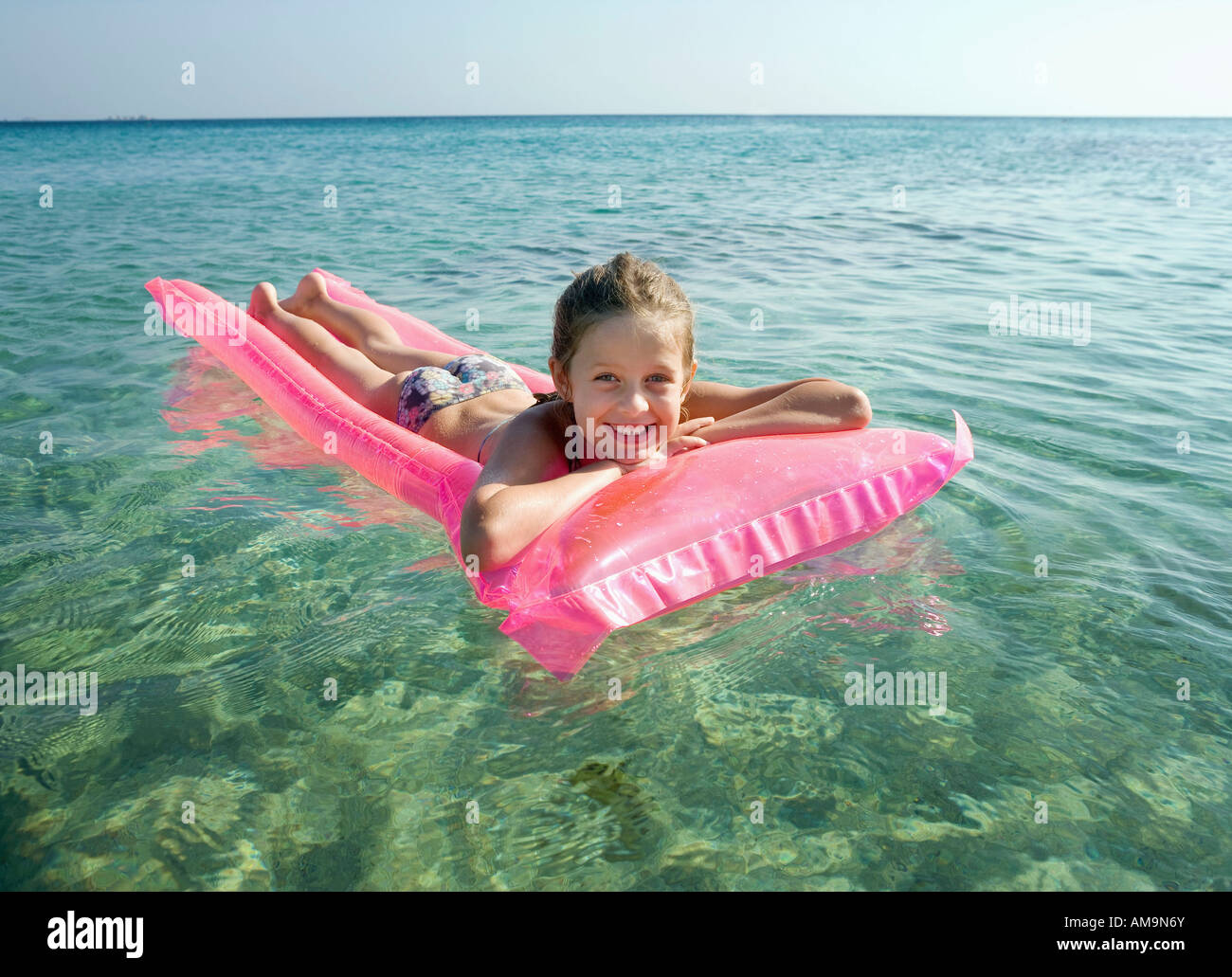Young girl on an inflatable raft in the water smiling. Stock Photo