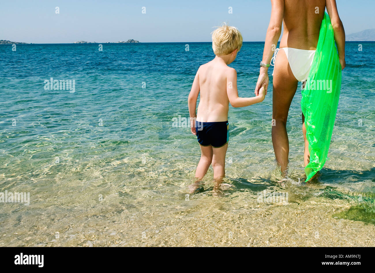 Woman holding inflatable raft with young boy on the beach. Stock Photo