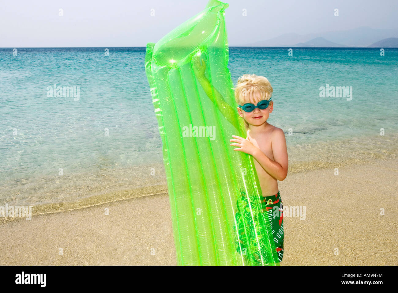 Young boy at the beach with an inflatable raft. Stock Photo