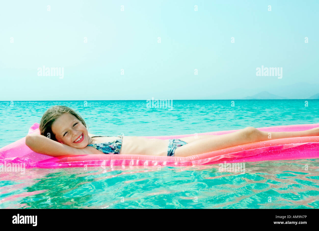 Young girl lying on inflatable raft in the water smiling. Stock Photo