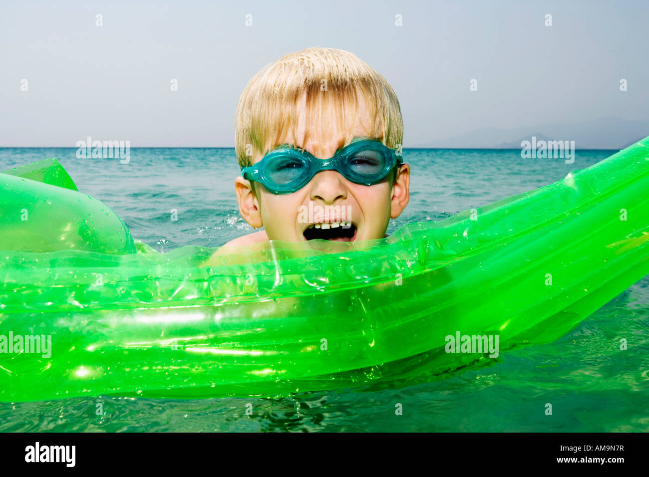 Young boy with an inflatable raft in the water with mouth open. Stock Photo