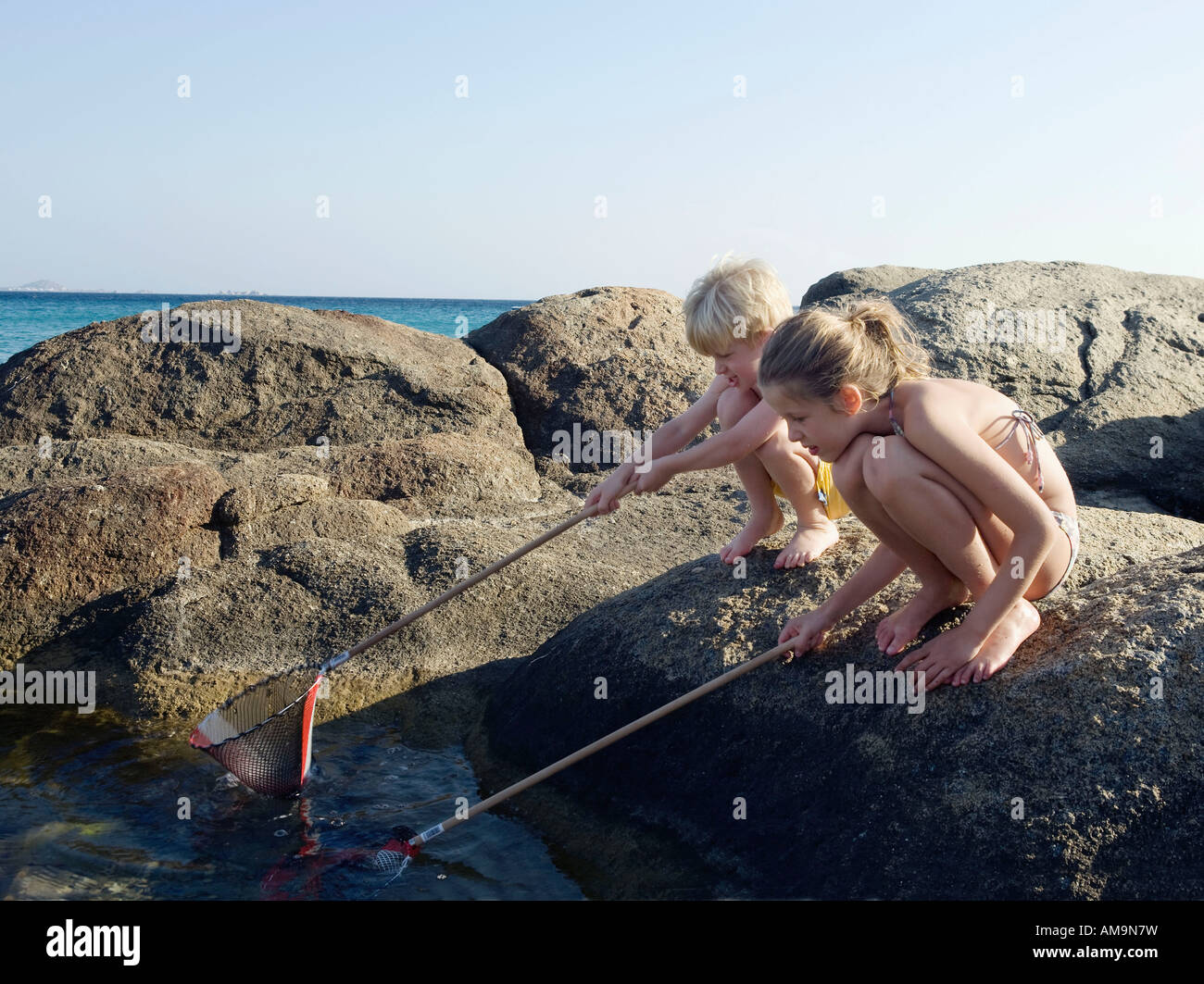 Young boy and young girl crouched on rocks fishing with nets. Stock Photo