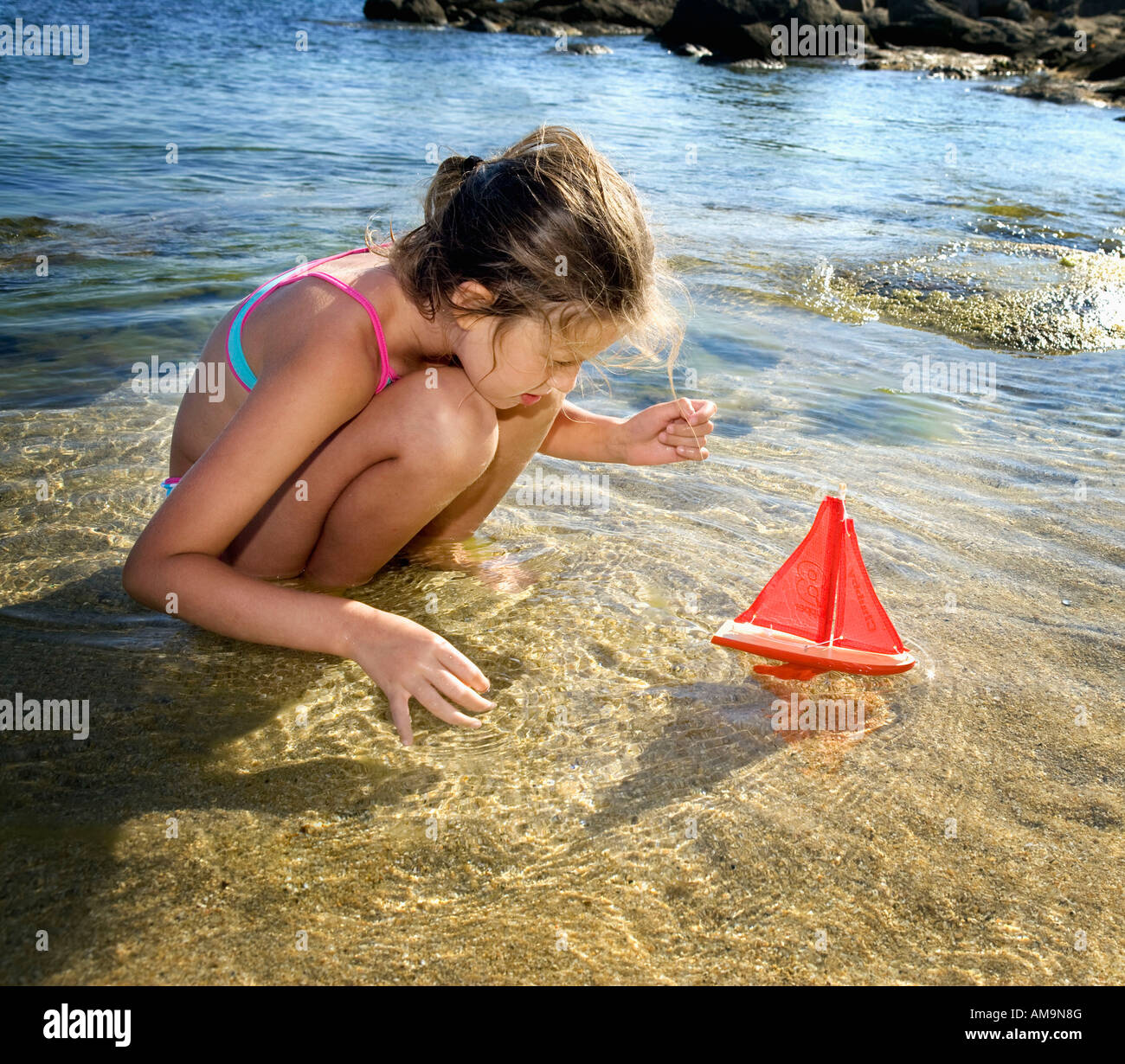 Young girl with a toy sailboat at the beach. Stock Photo