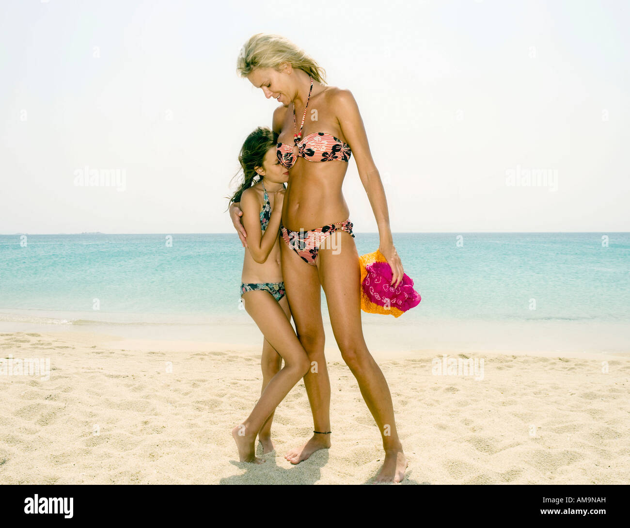 Woman and young girl at the beach smiling. Stock Photo