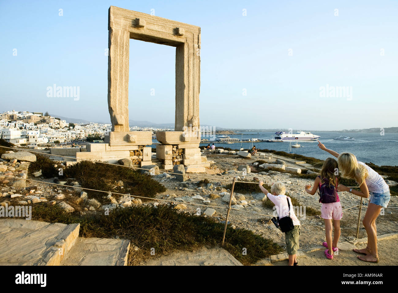 Woman with young boy and young girl pointing at the Portara in Greece with tourists in background. Stock Photo