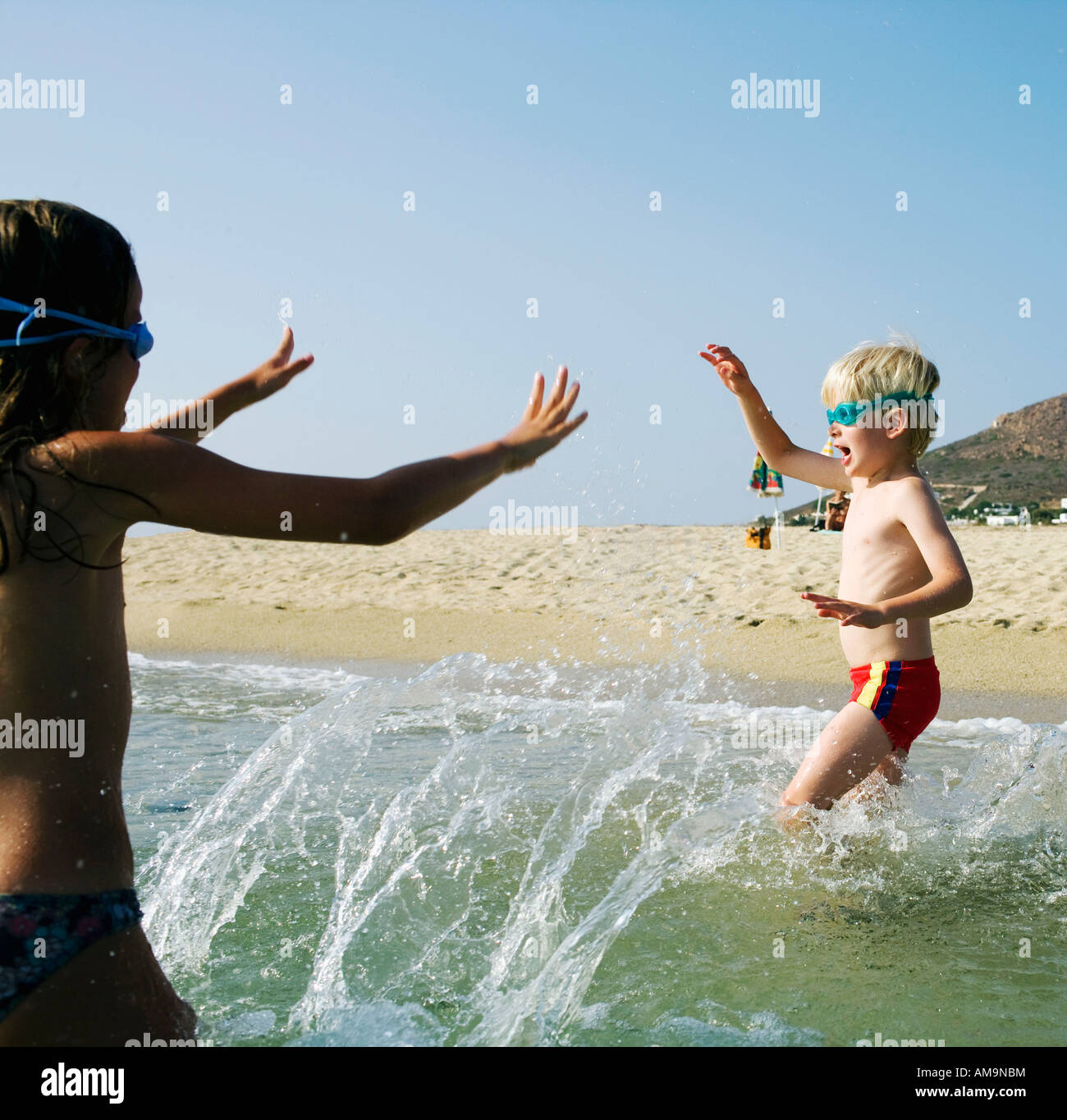 Young girl and young boy playing at the beach. Stock Photo