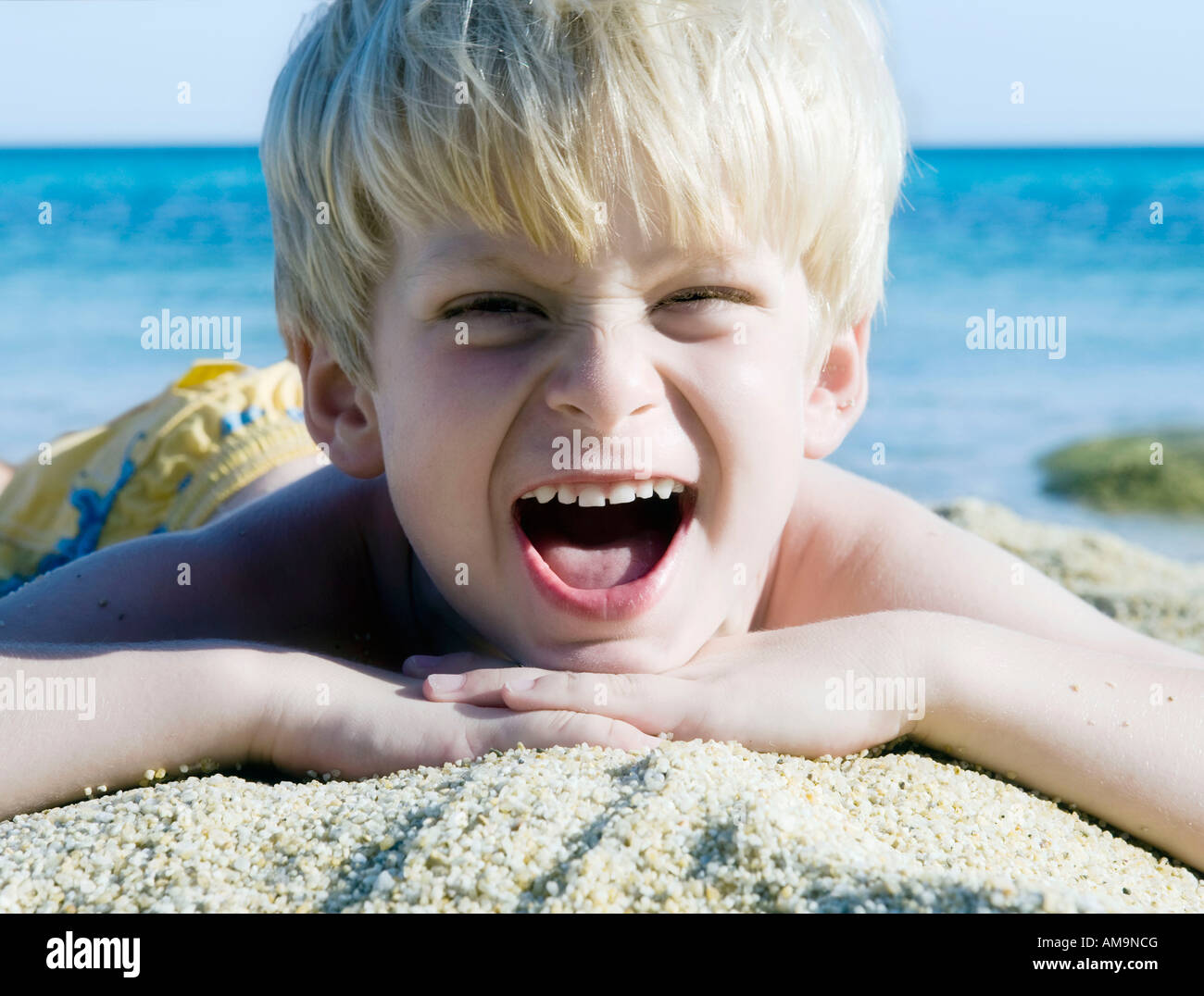 Young boy lying in the sand at the beach yelling. Stock Photo