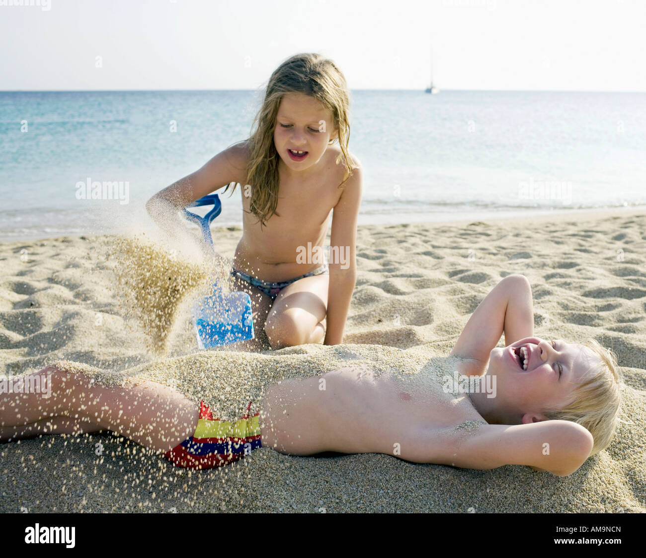 Young girl pouring sand onto a laughing young boy at the beach. Stock Photo