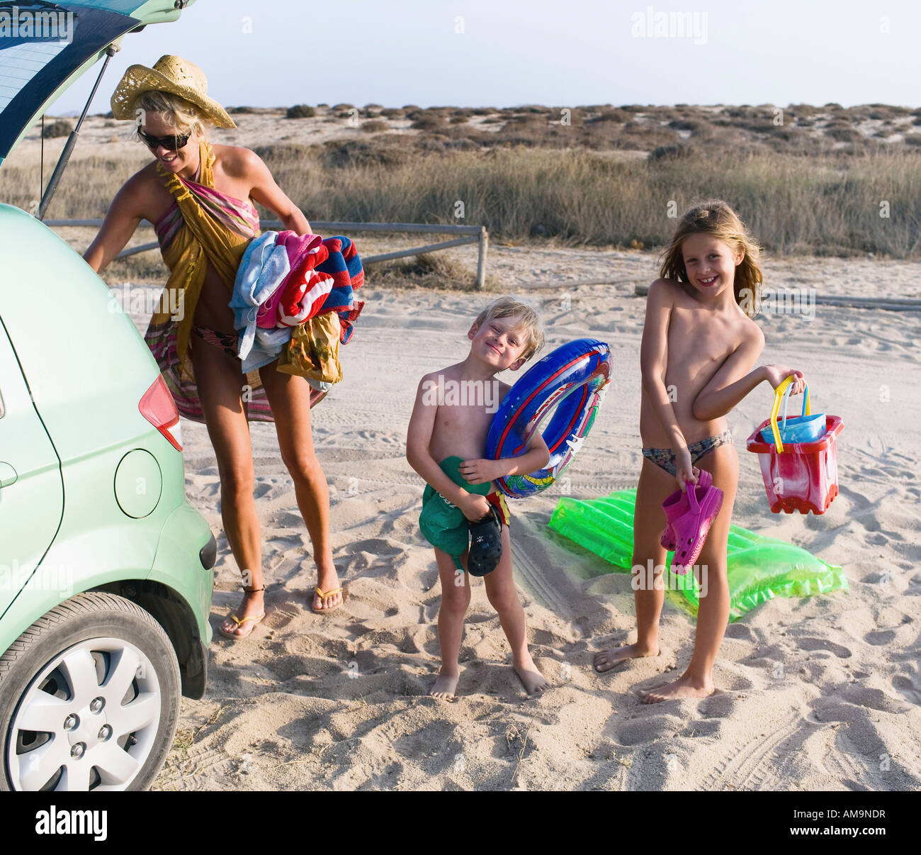 Woman with young boy and young girl arriving the beach. Stock Photo