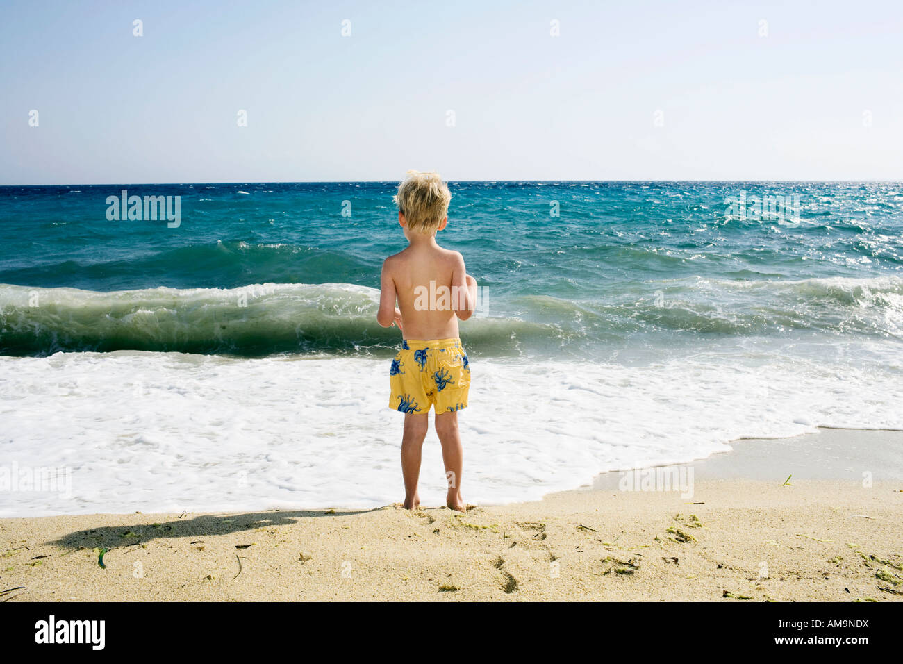 Young boy standing on the beach. Stock Photo